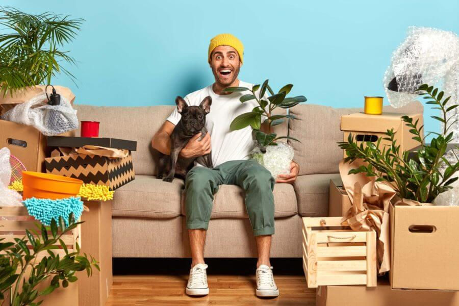 Young man is sitting in his living room on the sofa, hugging his pet, surrounded by plants and boxes