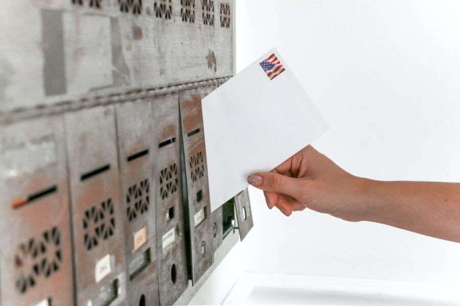 A person putting a white envelope in a mailbox