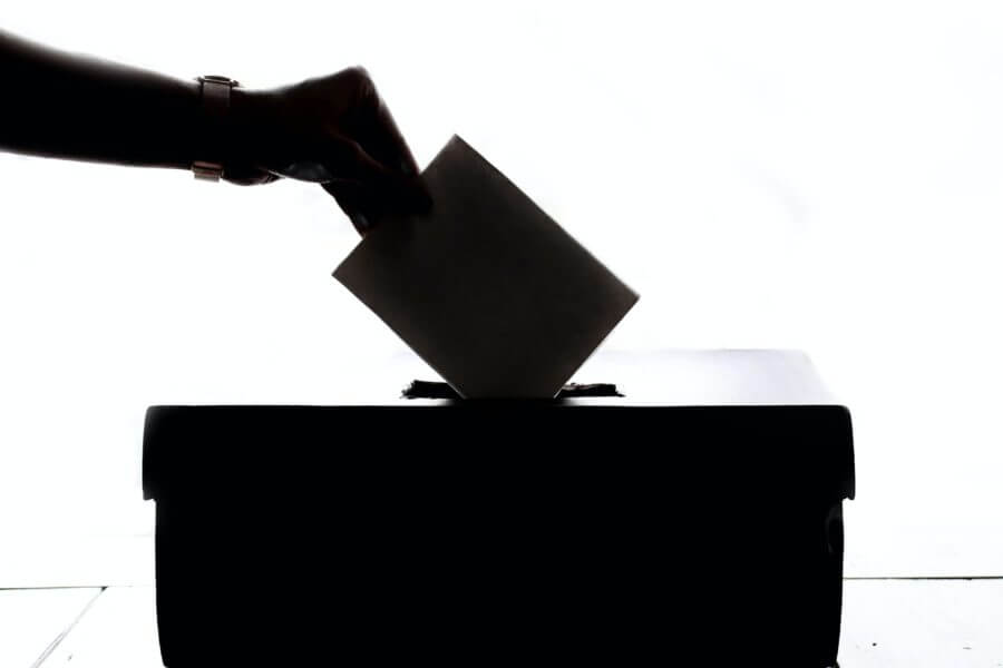 A hand dropping a ballot in the box