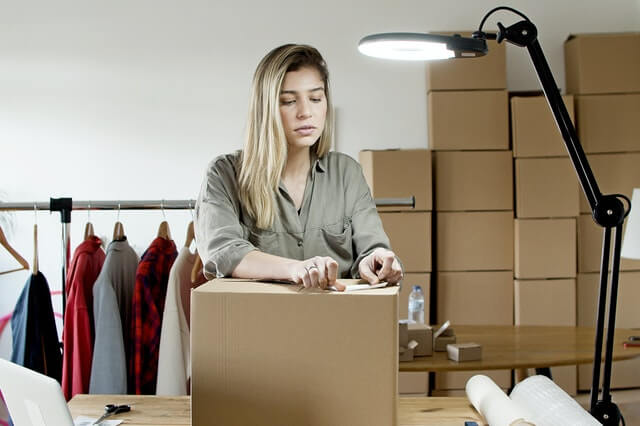 Girl packing a box for moving across country
