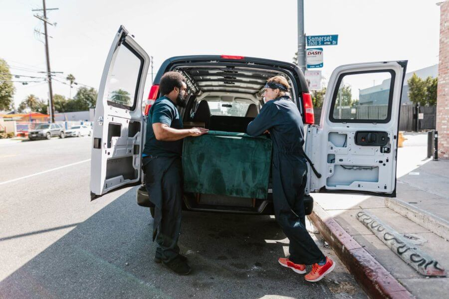 Men putting a couch in a long-distance moving van