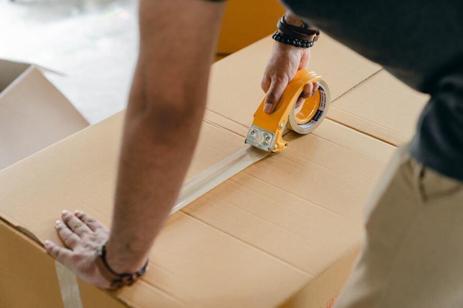 a man strengthening cardboard boxes with tape to prepare them for cross country moving