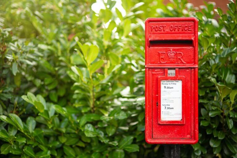 A red mailbox in front of a bush