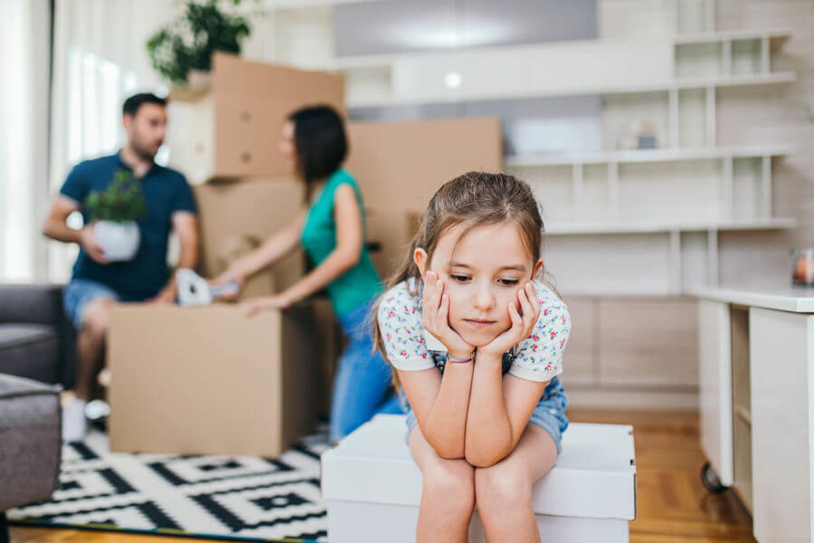 a sad little girl sitting on a moving box in front of her parents, unhappy about long-distance moving